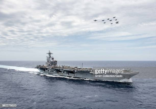 Photograph of aircraft flying in formation over the aircraft carrier USS George HW Bush during a joint training exercise involving US and French...