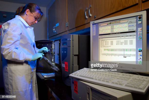 Photograph of Amanda McNulty a lab researcher at the CDC working on tests using the Siemens Trugene System to sequence HIV HBV and HCV DNA in order...