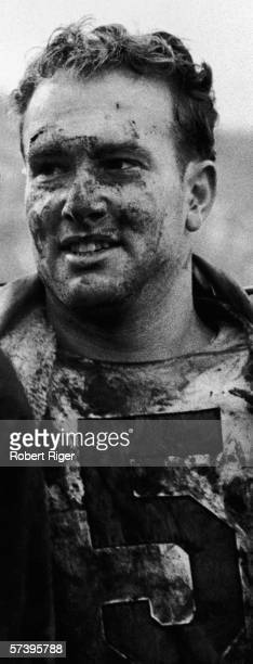 Photograph of American football player Paul Hornung of the Green Bay Packers as he stands covered in mud witha coat over his shoulders late 1950s or...