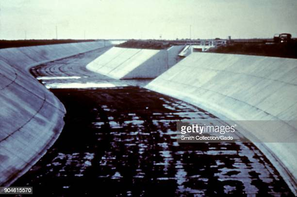 Photograph of an empty curved irrigation canal potential breeding ground for mosquitoes during rainy seasons and a site of concern for prevention of...
