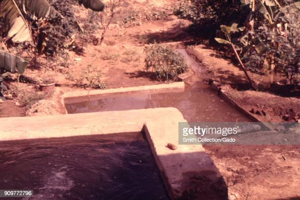 Photograph of an irrigation well with accumulated standing water potential breeding ground for vectorborne diseases in a field in Northern India 1974...