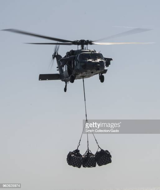 Photograph of an MH60s Seahawk navy helicopter towing pallets of cargo while in flight during a replenishmentatsea exercise May 15 2018