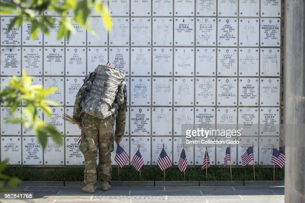 Photograph of an Old Guard soldier placing American flags in front of a Columbarium wall during the annual Flags In memorial ceremony Section 38...