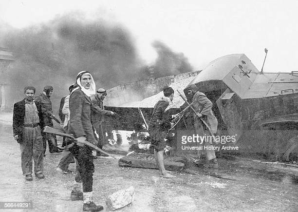 Photograph of Arab irregulars along with a burnt truck on the way to Jerusalem during the war of Independence Dated 1948