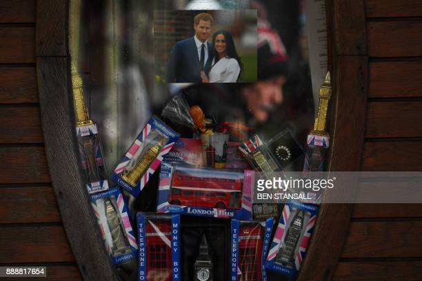 A photograph of Britain's Prince Harry and his financee US actress Meghan Markle adorns the window of a souvenir shop in London on December 9 2017...