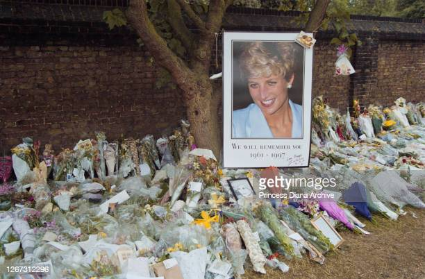 A photograph of British Royal Diana Princess of Wales with floral tributes and messages of condolence outside Kensington Palace in London England...
