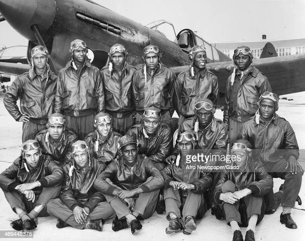 Photograph of Class SE 43 K newly commissioned pilots at Tuskegee Army Flying School in bomber jackets with a fighter airplane Tuskegee Alabama 1942