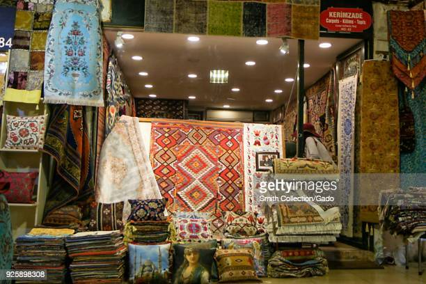 Photograph of colorful Oriental rugs and decorative pillows at the entrance to a market stall at Hasircilar Caddesi Istanbul Turkey November 11 2017