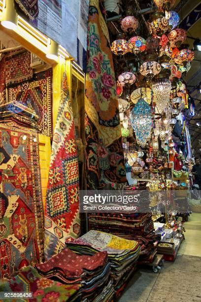 Photograph of colorful Oriental rugs and lanterns fronting market stalls at Hasircilar Caddesi Istanbul Turkey November 11 2017