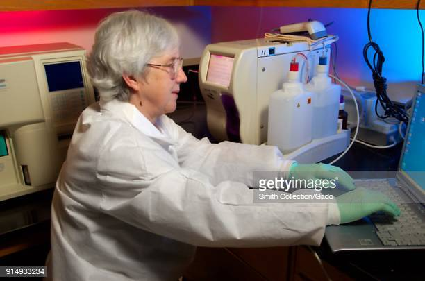 Photograph of Cynthia Warner a CDC Clinical Monitoring Team member in a working laboratory setting next to machines and a computer testing the...