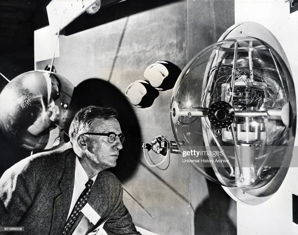 Photograph of Dr. A. V. Austin, director of the National Bureau of Standards and member of the U.S. National Committee for the International Geophysical Year, studying a cut-away model of the earth satellite to be launched by the United States. Dated 20th century.