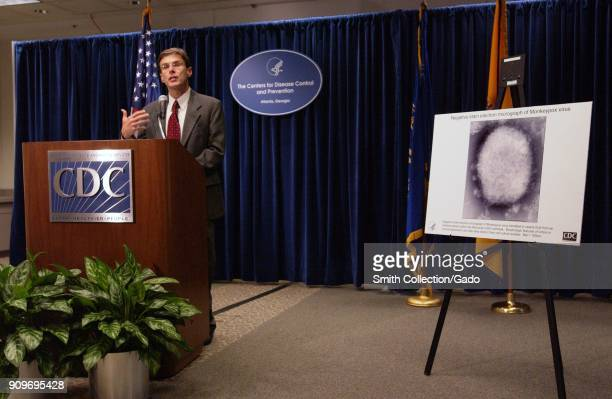 Photograph of Dr David Fleming addressing the press at a CDC briefing speaking from a lectern next to a poster as a visual aid in updating the public...