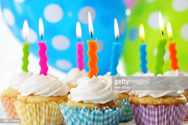 Photograph of eight cupcakes with candles