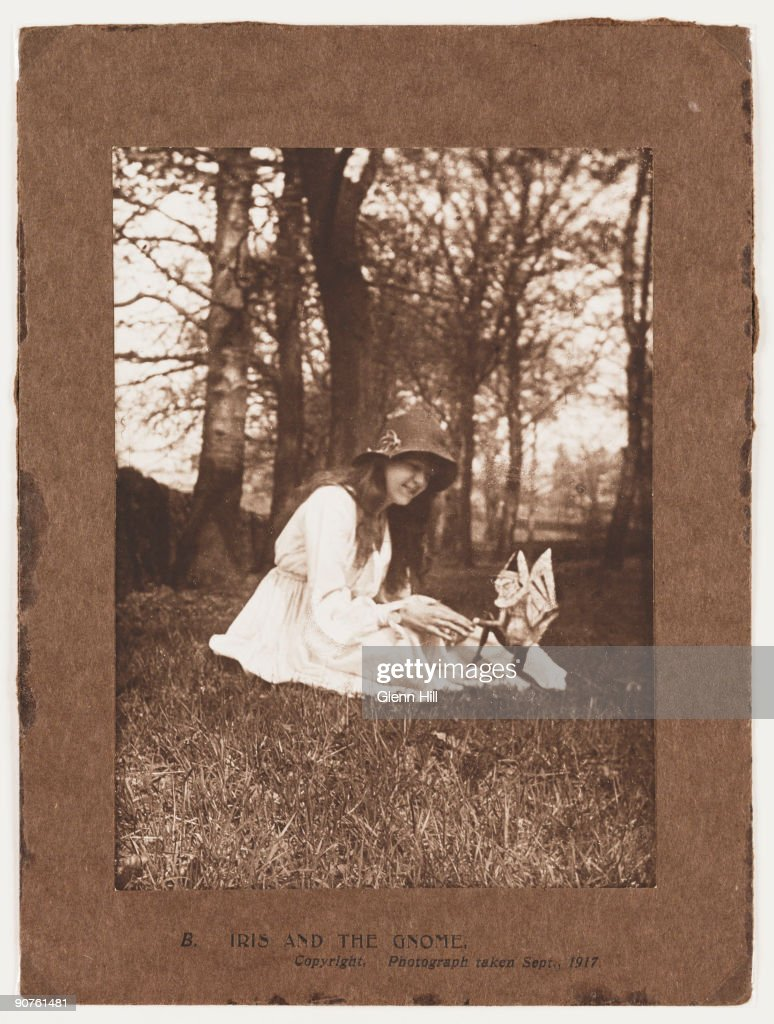 A photograph of Elsie Wright (1901-1988) taken by Frances Griffiths (1907-1986) using Elsie's father Arthur's Midg quarter-plate camera. This photograph is the second in the 'Cottingley Fairies' series. Elsie sits in the garden as a gnome dances towards her. At the time, this photograph provoked a bizarre public discussion. If studied closely, the point of a hat pin in the gnome's stomach - used to keep the cut-out standing - can be seen. Sir Arthur Conan Doyle (1859-1930), after examining the print, concluded that this pin point was a navel - sparking a discussion on methods of birth in the fairy kingdom. The story of the Cottingley Fairies began as a practical joke in Cottingley, near Bradford, West Yorkshire in 1917.