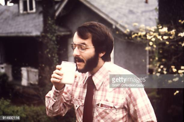 Photograph of epidemiologist Ed Baker standing outside a house examining a water sample taken as part of a study into contamination of the public...