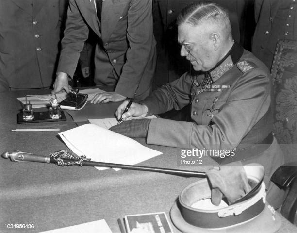 Photograph of Field Marshal Wilhelm Keitel signing the ratified surrender terms for the German military in Berlin Dated 1945