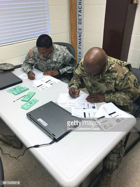 Photograph of Finance Corps members Cadet Ray Carter and Staff Sergeant Bobby Johnson filling out financial forms as part of disbursement training...