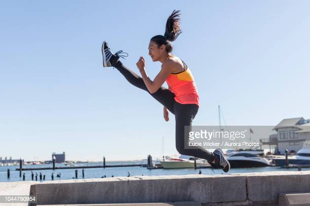 photograph of fit girl performing jumping kick, boston, massachusetts, usa - fitness or vitality or sport and women stock photos and pictures