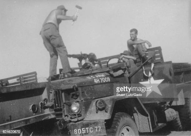 A photograph of four United States Army serviceman amusing each other on a parked M35 military truck two of the soldiers watch in amusement while a...
