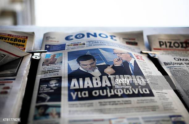 A photograph of Greek Prime Minister Alexis Tsipras with the President of the European Commission JeanClaude Juncker sits on the front of a newspaper...