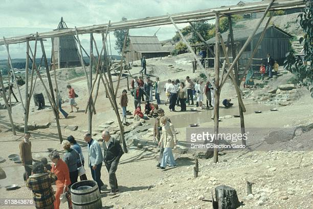 A photograph of groups of tourists touring Sovereign Hill the park depicts the towns first ten years of history after the discovery of gold in the...