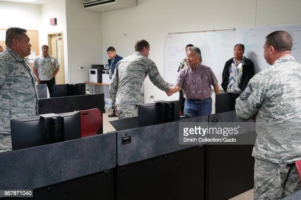 Photograph of Hawaiian governor David Ige shaking hands with Senior Airman Steven Bucholtz during a visit to the Task Force Hawaii Joint Operations...