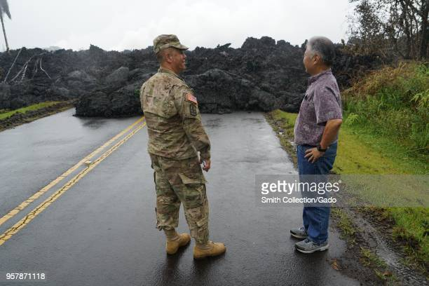 Photograph of Hawaiian governor David Ige with Brigadeer General Kenneth Hara standing near a mass of hardened lava during a tour of ground...