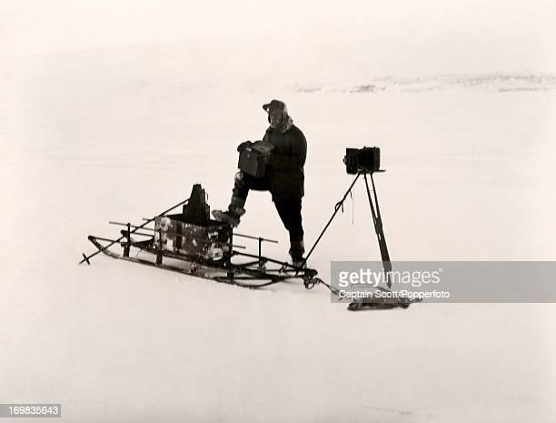 A photograph of Herbert Ponting at work on the sea ice near Cape Evans taken during the last tragic voyage to Antarctica by Captain Robert Falcon...
