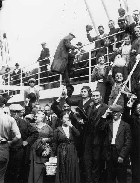 A Photograph of Immigrants Waving Aboard a Ship circa...