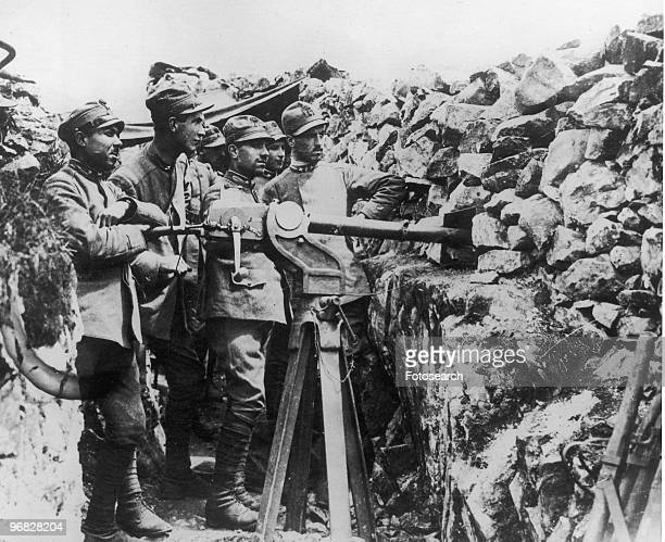 A Photograph of Italian Soldiers with a Gun on the Front Line in the Trenches waiting on instructions to fire circa 1915
