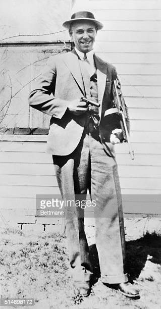 Photograph of John Dillinger notorious criminal taken shortly before he was killled He is posed with a Colt 38 in one hand and a submachine gun in...