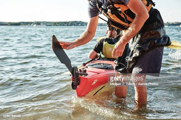 Photograph of kayak tour instructor lowering rudder on tandem sea kayak, Portland, Maine, USA
