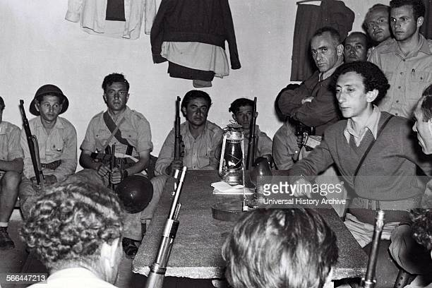 Photograph of Kibbutz Members meeting at a military briefing at Kibbutz Yad Mordechai during the Israel War of Independence One of the members...