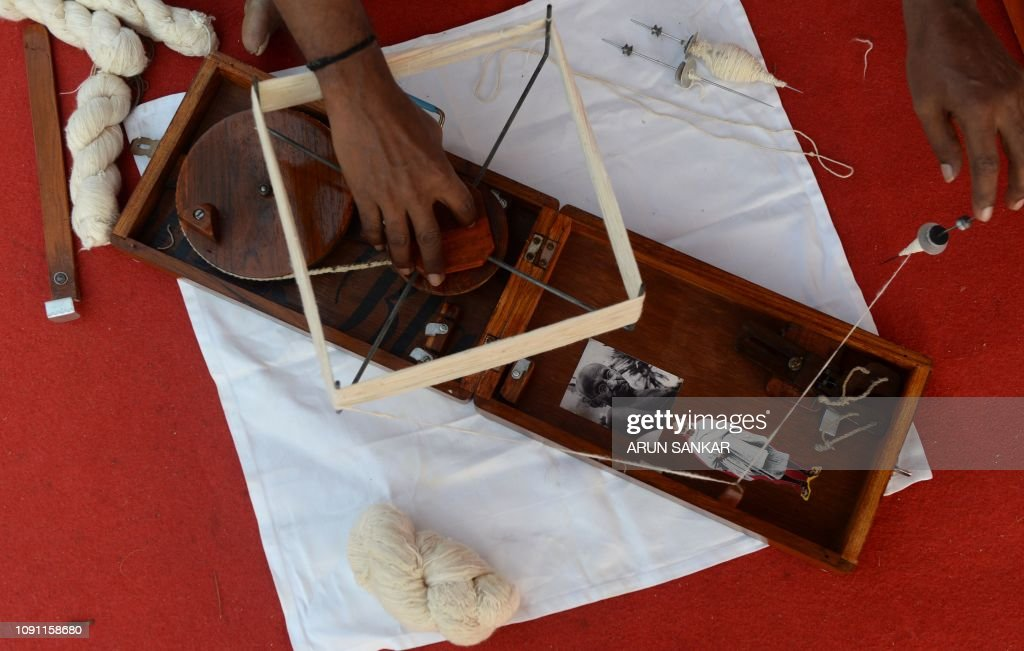 A photograph of Mahatma Gandhi is pictured on a 'charkha