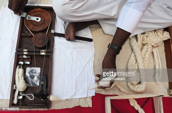 A photograph of Mahatma Gandhi is placed on a 'charkha