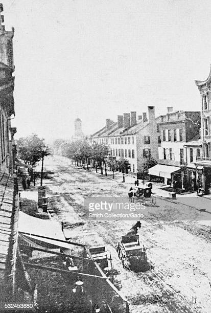 Photograph of Main Street in Lexington, horse drawn carriages are seen on the wide, unpaved street, the street is partially lined with trees,...