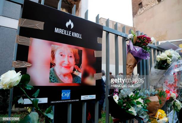 A photograph of Mireille Knoll and flowers are placed on the fence surrounding her building in Paris on March 28 in memory of the 85yearold Jewish...