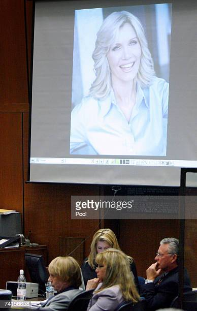 A photograph of murder victim Lana Clarkson is displayed on a screen as Phil Spector and defense team member Linda Kenny Baden listen to witness...