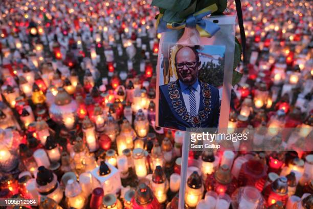 A photograph of murdered Gdansk mayor Pawel Adamowicz hangs over a sea of candles left by mourners on January 17 2019 in Gdansk Poland Adamowicz was...