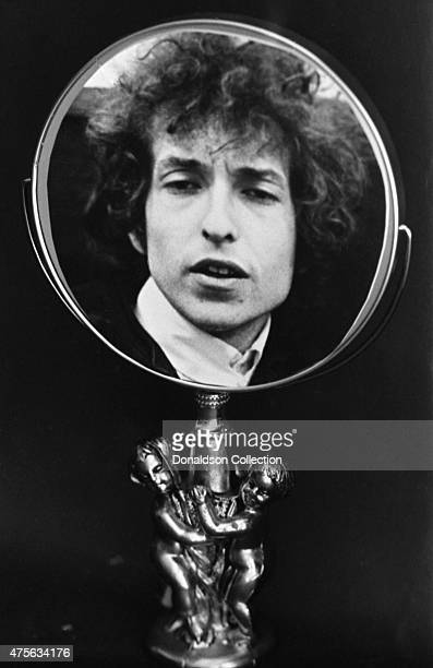 A photograph of musician Bob Dylan attached to an ornate mirror on a baset in 1966