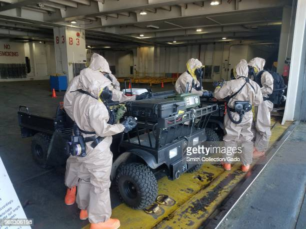 Photograph of National Guard service members wearing hazmat suits working next to a field vehicle during Vigilant Guard training exercises concerned...