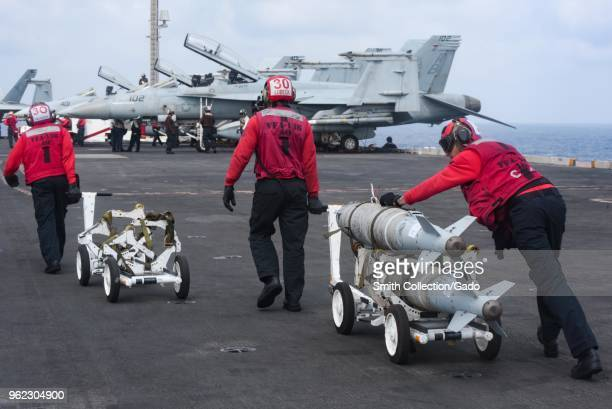 Photograph of navy sailors transporting bombs on the flight deck of the Nimitz-class aircraft carrier USS Harry S Truman, fighter jets visible in the...