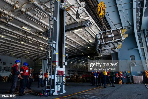 Photograph of navy soldiers receiving bombs in the hangar bay aboard the aircraft carrier USS Ronald Reagan during a replenishmentatsea May 15 2018