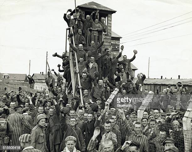 Photograph of Nazi concentration camp prisoners after being liberated. Photo shows the prisoners in their striped uniforms after climbing the guard...