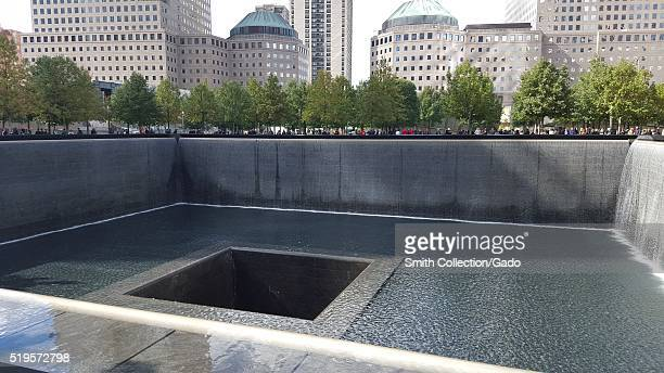 A photograph of one of two pools comprising the National September 11 Memorial in lower Manhattan with a crowd of tourists looking into the pool New...