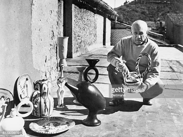 Photograph of Pablo Picasso exhibiting his painted ceramic works at his studio at Vallauris, France.