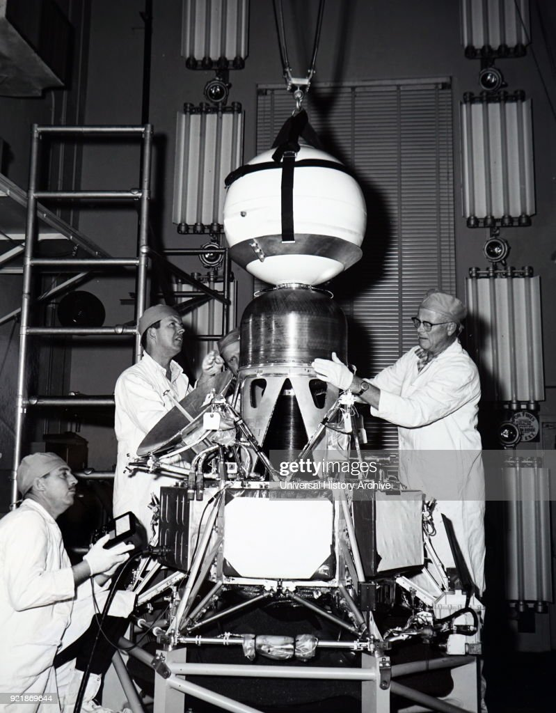 Photograph of payload engineers performing tests and installing a capsule and retro motor of Ranger III. Dated 20th century.