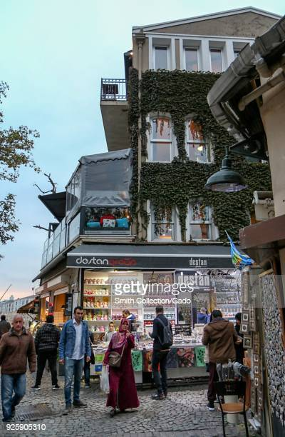 Photograph of pedestrians walking near a street market during the late afternoon Istanbul Turkey November 15 2017
