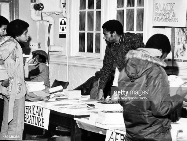 Photograph of people around bookstalls with books about black history and liberation, 1980.