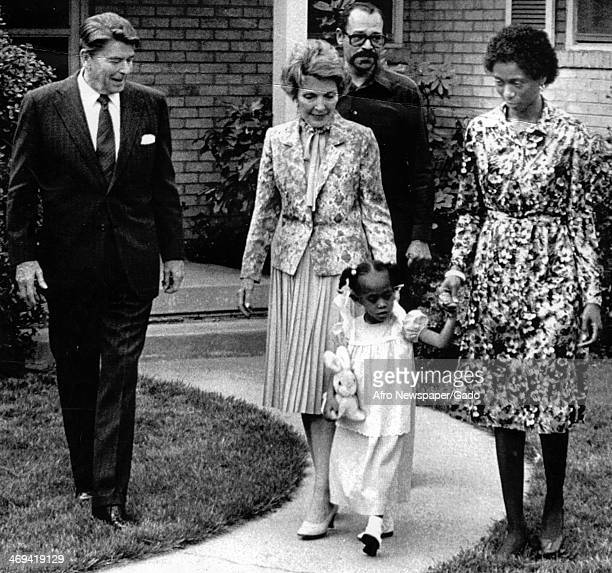 Photograph of President Ronal Reagan and his wife Nancy meeting with a family with one young daughter who were victims of the Ku Klux Klan,...